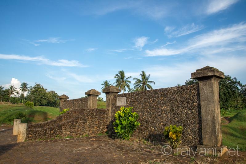 Tampak samping gapura dan disisi kiri dan kanan benteng tanah berupa bukit setinggi 3-4 m