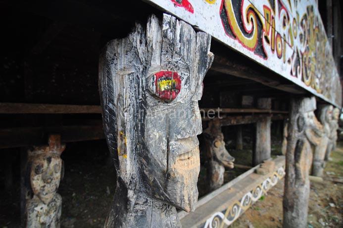 patung dayak di tiang kaki rumah betang east kalimantan